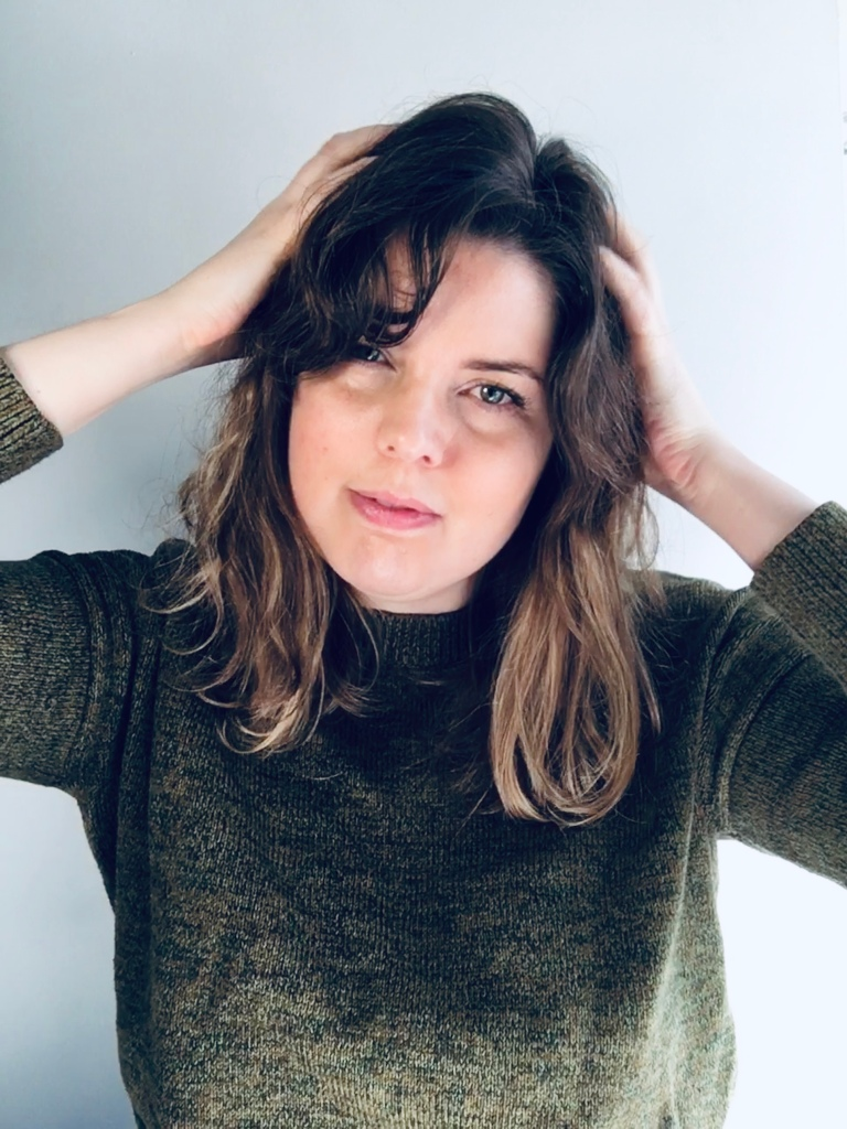 White woman wearing a dark green jumper smiles slightly looking into the camera. Her hair is long and dark brown on top, fading to blonde at the tips. She has her hands up in her hair. Background is a white wall.